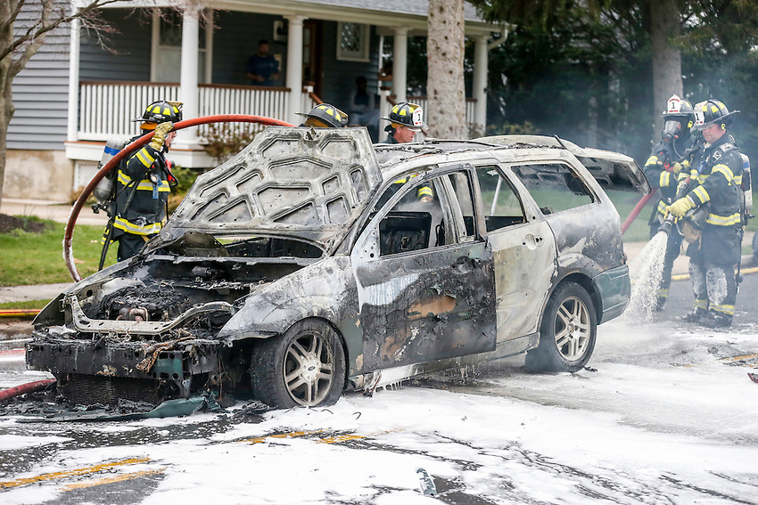 MANASQUAN, NJ — April 1, 2016 — Manasquan firefighters use foam to battle a car fire on Broad Street at about 9:40am Friday morning. The driver of the vehicle was not injured.  photo by Andrew Mills