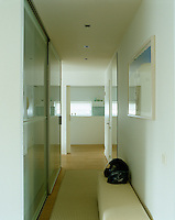 A glass wall and slding door coupled with cool tones of white and beige make the most of the available light and space in a long narrow corridor