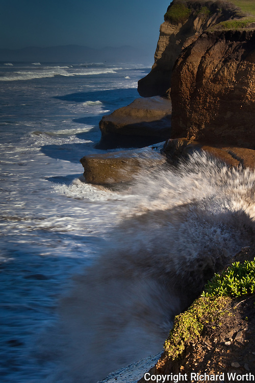 Waves crash into the bluffs at Pomponio State Beach throwing sand-brown spray into the air.