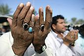 KARBALA, IRAQ: A Shia pilgrim brings his hands up in prayer...Shia pilgrims pray during the last day of the Ashura festival...Photo by Metrography