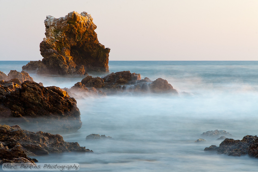 A long-exposure shot taken just before sunset at Little Corona beach in Corona Del Mar (Newport Beach), CA, aiming at the distinctive arch rock off shore.  The water almost looks like fog, and I like how you can see the water cascading over the middle rock.