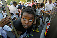 Ethiopian Jewish kid stares at the lens while Ethiopian Jewish  immigrants dance and celebrate while holding Torah Scrolls during an inauguration ceremony for a new Ethiopian Spiritual Center in Jerusalem, on June 23, 2013. The new center was funded by The International Fellowship of Christians and Jews. Photo by Oren Nahshon