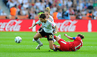 Linda Bresonik (l) and Kim Kulig (C) of Germany and Christine Sinclair of Canada during the FIFA Women's World Cup at the FIFA Stadium in Berlin, Germany on June 26th, 2011.