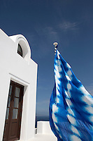 A sail in tie & dye Savine linen by Designers Guild flutters from a pole at the entrance to this Greek villa