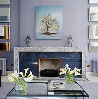The focal point of this living room is the stunning contemporary fireplace with a hearth constructed from grey veined marble and a grate set in a surround of deep blue glass