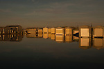 Boathouse reflections in rows along the waterfront at Everett Marina with moon setting