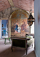 Beneath the painted ceiling of the entrance hall an old stone wall is nearly covered by a large antique religious painting