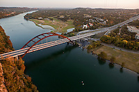 Aerial view from a helicopter of the 360 Bridge or Pennybacker Bridge The bridge spans across Lake Austin and connects the Capitol of Texas Highway (Loop 360). You can see downtown Austin off to the left on the horizon.