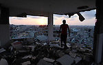 A Palestinian man sits inside his destroyed house after returning home in the Tufah neighbourhood in eastern Gaza City on August 31, 2014. Calm returned to the coastal enclave in a August 26 ceasefire, and Gazans were gradually starting to rebuild their lives after a bloody and destructive 50-day war, the deadliest for years. Photo by Ashraf Amra