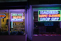 Night view of a carpet store and restaurant with bright neon signs.