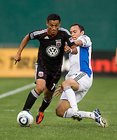 Andy Najar (14) of D.C. United tries to get past the tackle of Ramiro Corrales (12) of the San Jose Earthquakes celebrates his first goal during the game at RFK Stadium in Washington, DC.  D.C. United was defeated by the San Jose Earthquakes, 4-2.