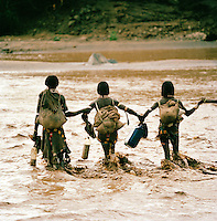 Hamer tribesman fording river in Turmi, Lower Omo Valley, Ethiopia