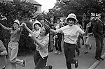 Belfast Orange Day Parade,  teen girls dancing through the street with Union Jack flags. 1970