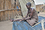A woman displaced from the Darfur region of Sudan braids rope in the Goz Amer refugee camp in eastern Chad. More than a quarter million residents of Darfur live in camps in Chad, along with almost 200,000 Chadians who have been internally displaced by related violence.