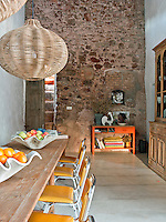 In the dining room the old has been juxtaposed with the new; the double height original stone wall has been left exposed and the floor has been covered in smooth polished concrete