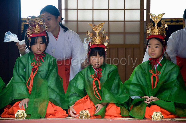"""Young """"yaotome"""" female performers are cooled down with ice packs by maiko shrine attendants as they kneel in an antechamber during a ritual in the main hall of Tsurugaoka Hachimangu shrine during the second day of the 3-day Reitaisai grand festival in Kamakura, Japan on  15 Sept. 2012.  Photographer: Robert Gilhooly"""