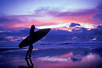 Woman heading for the water with surfboard in hand on the North Shore of Oahu