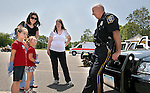 TORRINGTON, CT. 04 JUNE 2011 -060411JW03-- Rosannne Field, of Torrington and Karin Obegenski of Harwinton look on as Torrington Police Office Ron Currier Talks with Rebecca Obegenski age 6 and Rachel Obegenski age 4 about the importance of wearing your seatbelts during the Torrington Parks and Recreation Department and the Torrington Municipal and Teachers Credit Union second annual Magic Motion event Saturday afternoon at Torrington High School.<br /> Jonathan Wilcox Republican-American