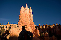 """The sun rises over the """"hoodoos"""" of Bryce Canyon National Park in southern Utah. The odd limestone formations erode out of the cliffs in the area, and gain their red, orange and yellow colors from oxidizing minerals in the stone. Hiker Paul Orosz, of Denver, gazes on the sight."""
