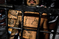 "A member of the Mara Salvatrucha gang (MS-13) stands behind the bars in a cell at the detention center in San Salvador, El Salvador, 20 February 2014. Although the country's two major gangs reached a truce in 2012, the police holding cells currently house more than 3000 inmates, five times more than the official built capacity. Partly because the ordinary Mara gang members did not break with their criminal activities (extortion, street-level distribution of drugs, etc.), partly because Salvadorean police still applies controversial anti-gang law which allows to detain almost anyone for ""suspicion of gang membership"". Accused young men are held in police detention centers where up to 25 inmates may share a cell of five-by-five metres. Here, in the dark overcrowded cages, under harsh and life-threatening conditions, suspected gang members wait long months, sometimes years, for trial or for to be transported to a regular prison."