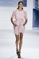 Claire de Regge walks runway in a rose super pique sleeveless peplum coat with oversized hood and cutout pocket over rose silk chiffon eyelet dress.by Vera Wang, for the Vera Wang Spring 2012 collection, during Mercedes-Benz Fashion Week Spring 2012.