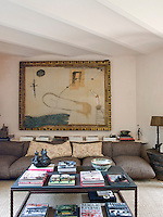 A large mixed media canvas is the focal point of the living room with a large slate-topped metal coffee table
