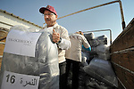 Saad Gedeon (left) and Felomain Nassar-Batshone, program staff of the Jordan program of International Orthodox Christian Charities, help unload bundles of new uniforms for students in the Zaatari Refugee Camp, located near Mafraq, Jordan. Opened in July, 2012, the camp holds upwards of 50,000 refugees from the civil war inside Syria. International Orthodox Christian Charities, which provided the uniforms, and other members of the ACT Alliance are active in the camp providing essential items and services.