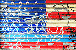 A peeling graffiti of the American flag on a metal door. Manhattan,  New York City.