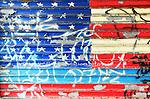 A peeling graffiti of the American flag on a metal door. Manhattan,  New York City.