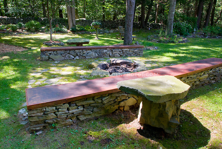 Great backyard with homemade Firepit next to long stone benches with wooden top and slate stone tables under trees in wooded garden landscaping, for large family gatherings