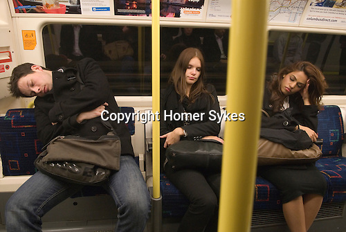 London Underground  subway asleep on a tube train late at night. London Uk.