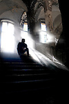 Man sitting on some stairs on old hospital with sunlight streaming through window
