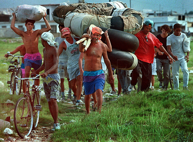 8/19/1994-Al Diaz/Miami Herald--In 1994 Cuban balseros turned the tiny fishing village of Cojimar into a major point of embarkation for thousands seeking a better life. Here,Cubans carring their homemade rafts, walk along a rocky trail on their way to the shore line of Cojimar, Cuba.