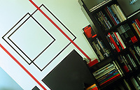 The walls of the living room are decorated with geometric lines, their disorientating slant emphasised by a bookshelf hanging at a 45-degree angle on the wall