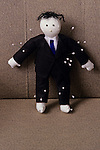 Voodoo doll standing in chair in office dressed as a business man in a black suit and blue tie with pins stuck in his body