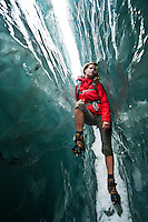 Beautiful woman walking through deep and  beautiful ice crevasse on Franz Josef Glacier - Westland National Park, West Coast, New Zealand