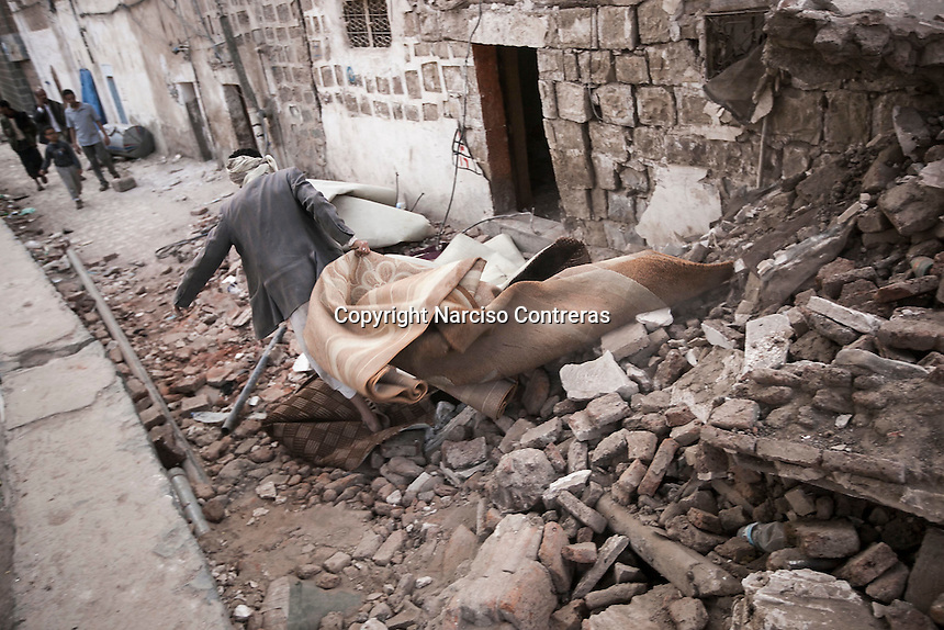 Thuesday 09 July, 2015: A man collects his belongings from the rubble of his house after it was targeted by a bomb dropped by a fighter jet of the Saudi-led coalition in the old city of Sana'a last June 2015. (Photo/Narciso Contreras)