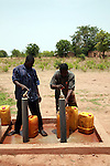 Men filling tanks with guinea worm-free water. A cloth filter was placed at the end of the tap. Water will be sold in town. Savelugu, Northern Region, Ghana.
