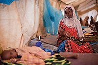 Fatuma Badel fled Buale, Somalia with 8 children after leaving her sick husband. &quot;He became sick and I couldn't carry him. I don't know if he is alive or dead. This one, my youngest child was like a dead person when I arrived. Now I thank God I can hear him cry again.&quot;  Badel has spent 3 days in the Doctors Without Borders hospital with her baby Mohamud who arrived severely malnourished. At nine months old he weighs 4.3 KG. Dadaab refugee camp, Kenya July 22, 2011. Photo: Brendan Bannon