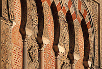 Architectural detail of the Puerta de San Ildefonso, built under Al-Hakam II in the 10th century, one of the West facade entrances to the Cathedral-Great Mosque of Cordoba, on the Calle Torrijos in Cordoba, Andalusia, Southern Spain. This detail shows an overlapping arch design with red brick, mosaic work and intricately carved vegetal patterns. The first church built here by the Visigoths in the 7th century was split in half by the Moors, becoming half church, half mosque. In 784, the Great Mosque of Cordoba was begun in its place and developed over 200 years, but in 1236 it was converted into a catholic church, with a Renaissance cathedral nave built in the 16th century. The historic centre of Cordoba is listed as a UNESCO World Heritage Site. Picture by Manuel Cohen