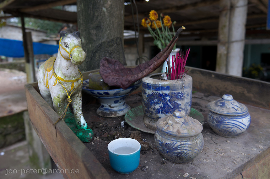 little shrine with offerings and chinese porcelain goods at the streets outside city Hue, Vietnam. Vietnamese belief is a blend of Buddhism, Taoism and animism.