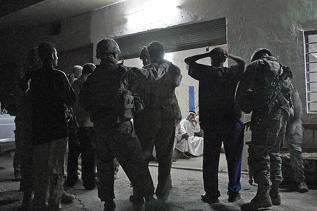 U.S. soldiers with Troop A, 3rd Squadron, 1st Cavalry Regiment detain two suspected members of a Shiite insurgent militia during a raid in the Four Corners area southeast of Baghdad, Iraq. Sept. 13, 2007. DREW BROWN/STARS AND STRIPES