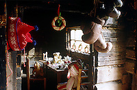 A seasonal woollen hat and simple Christmas wreaths adorn this country kitchen where three teddy bears are being served with tea