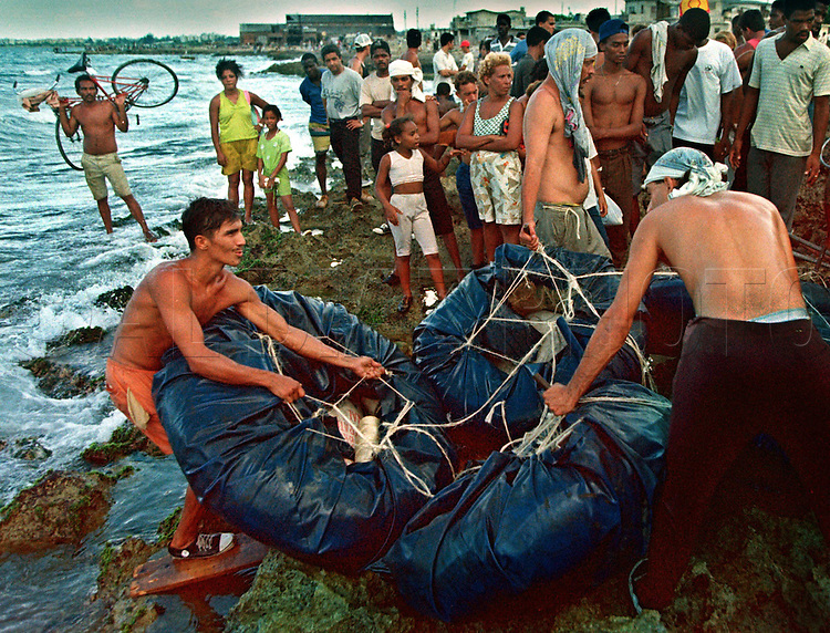 8/1994-Al Diaz/Miami Herald--In 1994 Cuban balseros turned the tiny fishing village of Cojimar into a major point of embarkation for thousands seeking a better life. Here, Cubans struggle to get their raft to water across the jagged shoreline of Cojimar.