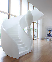 The curved plaster staircase and sculpture in the spacious living room are custom designs