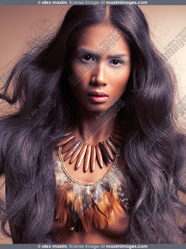 Ethnic beauty portrait of a young woman with long dark hair wearing feather necklace