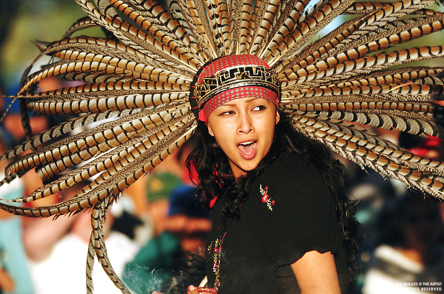 Vance Green / IPT.Elizabeth Flores, of Caldwell, chants and dances Monday evening during a performance by Danza Azteca De Caldwell, a traditional Aztec dance group. The group was one of the many performances that took place during a candlelight vigil in support of immigrant rights..Monday, May 1, 2006
