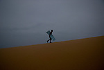 A Vietnamese boy walks through the sand dunes of Mui Ne with his sled looking for the right one to slide down in Vietnam.
