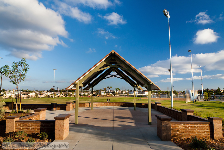 A wide view of the bandstand at Stanton Central Park, showing the baseball field and soccer fields behind it, all under a gorgeous blue sky with puffy white clouds.