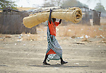 A displaced woman carries a woven mat in Agok, a town in the contested Abyei region where tens of thousands of people fled in 2011 after an attack by soldiers and militias from the northern Republic of Sudan on most parts of Abyei. Although the 2005 Comprehensive Peace Agreement called for residents of Abyei--which sits on the border between Sudan and South Sudan--to hold a referendum on whether they wanted to align with the north or the newly independent South Sudan, the government in Khartoum and northern-backed Misseriya nomads, excluded from voting as they only live part of the year in Abyei, blocked the vote and attacked the majority Dinka Ngok population. The African Union has proposed a new peace plan, including a referendum to be held in October 2013, but it has been rejected by the Misseriya and Khartoum.